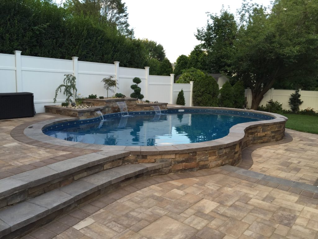 semi in-ground pool with brick landscaping